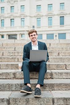 Retrato, de, um, sucedido, jovem, homem negócios, sentar escada, com, laptop