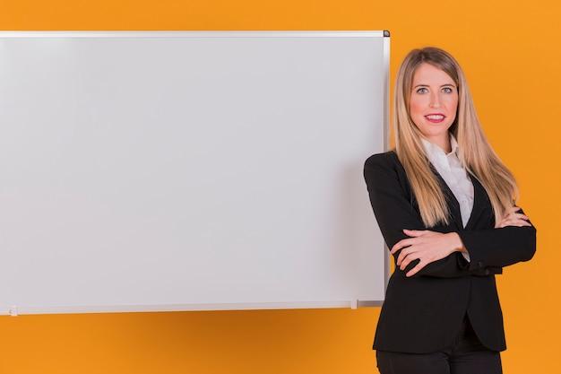 Retrato, de, um, sucedido, jovem, mulher negócios fica, perto, a, whiteboard, contra, um, laranja, fundo