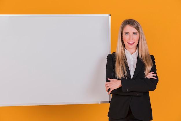 Retrato, de, um, sucedido, jovem, mulher negócios fica, perto, whiteboard, contra, um, laranja, fundo