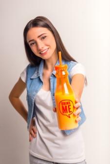 Retrato de um suco bebendo da menina alegre do adolescente.
