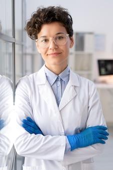 Retrato de um técnico de laboratório atraente com óculos e luvas em pé com os braços cruzados na sala de laboratório