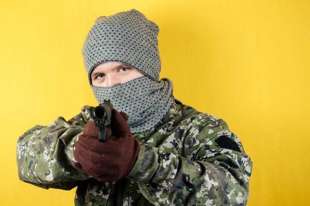 Retrato de um terrorista que atira em uma camuflagem e uma máscara segurando uma arma na mão