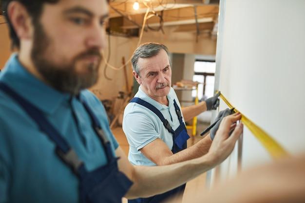 Retrato de um trabalhador da construção civil sênior medindo a parede durante a reforma da casa com o estagiário