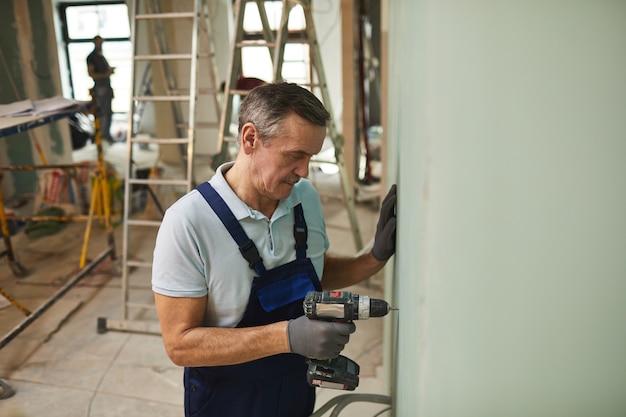 Retrato de um trabalhador da construção civil sênior perfurando a parede enquanto reforma a casa sozinho, copie o espaço