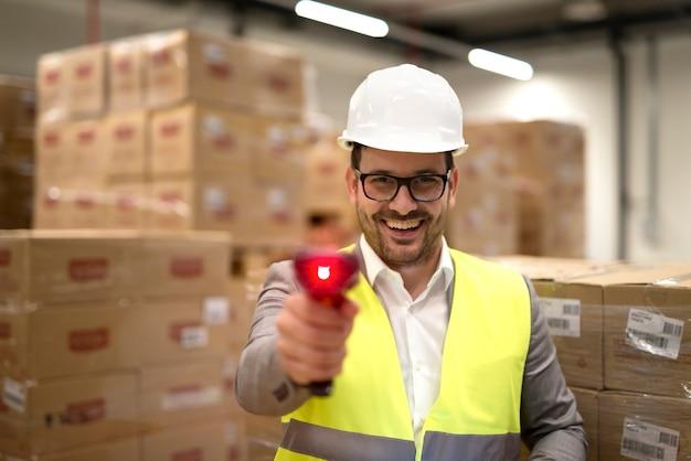 Retrato de um trabalhador de armazém de fábrica parado entre caixas de papelão segurando o feixe de laser do leitor de código de barras apontando para a câmera