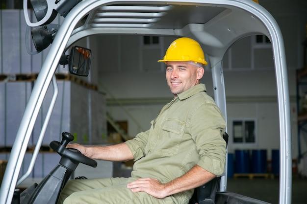 Retrato de um trabalhador de armazém masculino feliz no capacete de segurança, dirigindo uma empilhadeira no armazém, segurando o volante, sorrindo, olhando para longe