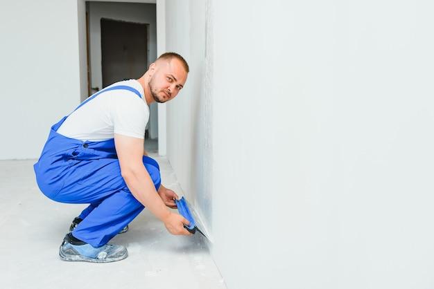Retrato de um trabalhador de macacão e segurando uma espátula nas mãos contra o fundo da parede gessada. trabalho de reparo e conceito de construção