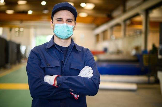 Retrato de um trabalhador em uma planta industrial usando uma máscara, conceito de coronavírus