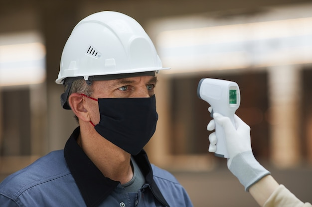 Retrato de um trabalhador maduro usando máscara e esperando para medir a temperatura com termômetro sem contato no canteiro de obras, segurança contra vírus corona