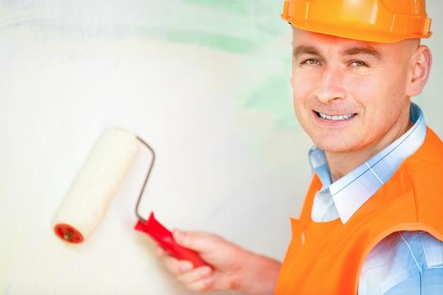 Retrato de um trabalhador pinta um rolo de parede para pintar