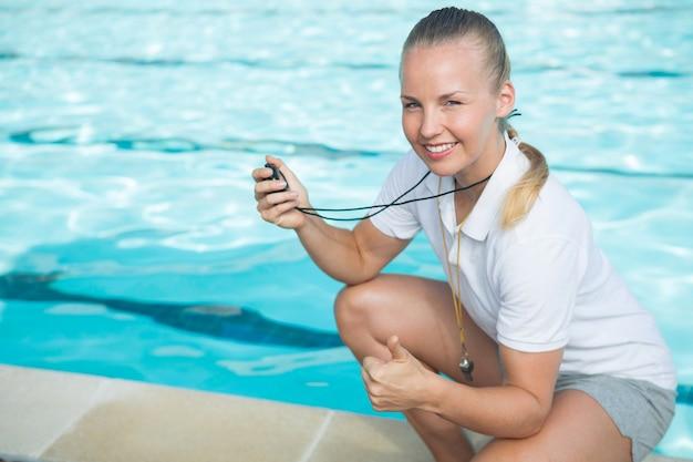 Retrato de um treinador de natação sorridente segurando um cronômetro e mostrando os polegares para cima à beira da piscina