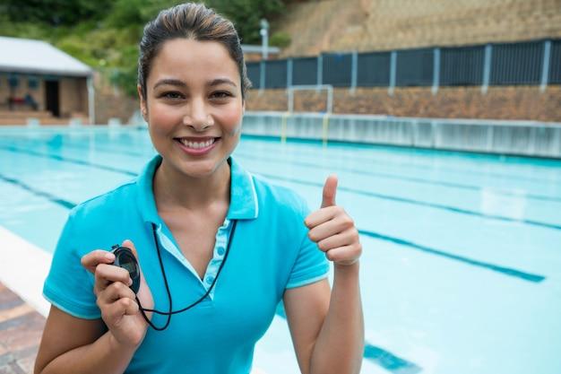 Retrato de um treinador de natação sorridente segurando um cronômetro e mostrando os polegares perto da piscina