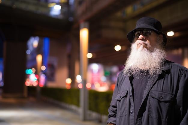 Retrato de um turista barbudo maduro explorando as ruas da cidade de bangkok, na tailândia, à noite