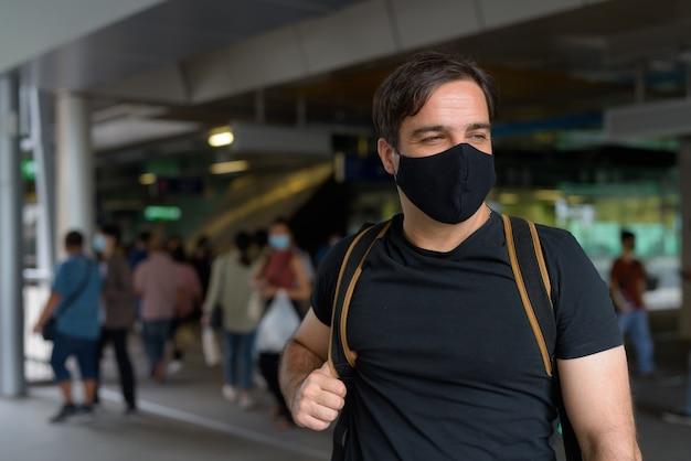 Retrato de um turista persa com máscara para proteção contra surto do vírus corona na estação de trem do céu