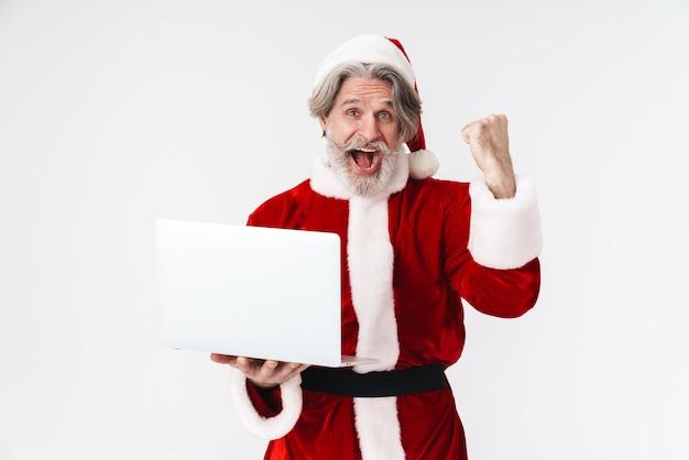 Retrato de um velho encantado vestindo uma fantasia vermelha de papai noel fazendo gesto de vencedor e usando laptop isolado no branco