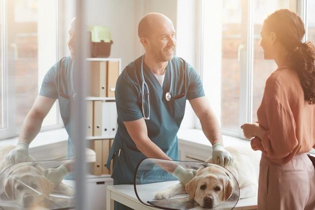 Retrato de um veterinário maduro examinando um cachorro na clínica veterinária e sorrindo enquanto falava com uma jovem, cena iluminada pela luz do sol, copie o espaço
