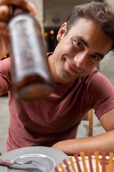 Retrato de um viajante masculino segurando uma garrafa de cerveja