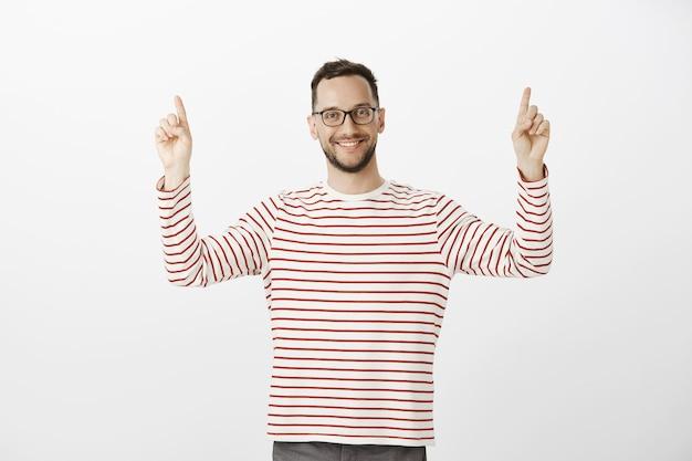 Retrato de um vizinho simpático e bonito com óculos da moda, levantando o dedo indicador e apontando para cima