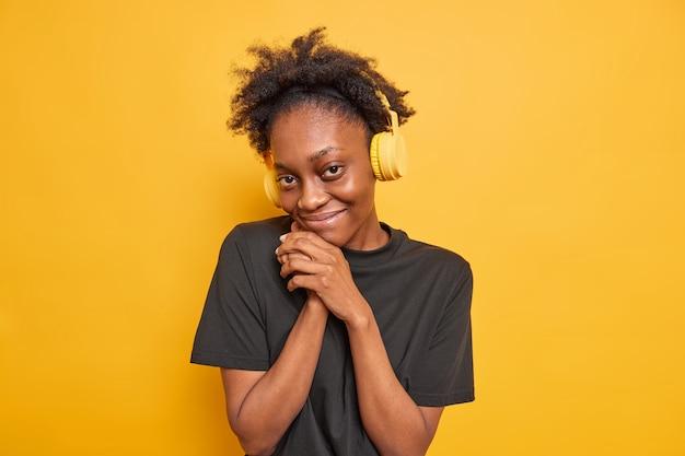 Retrato de uma adolescente afro-americana de boa aparência satisfeita e tímida mantém as mãos perto do rosto e parece satisfeita com a câmera