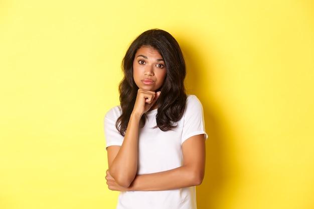 Retrato de uma adolescente afroamericana entediada e desanimada, relutante em olhar para a câmera em pé.