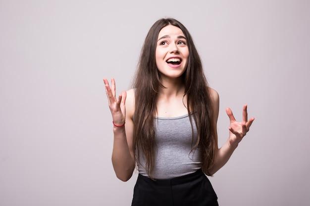 Retrato de uma adolescente alegre e feliz, vestida com uma jaqueta jeans, comemorando o sucesso enquanto dança isolada