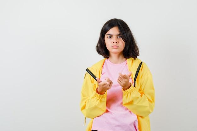 Retrato de uma adolescente apontando para uma camiseta, jaqueta e olhando sério.