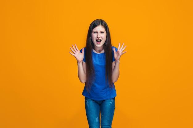 Retrato de uma adolescente com raiva em um estúdio laranja