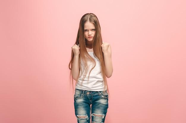 Retrato de uma adolescente com raiva em uma parede rosa