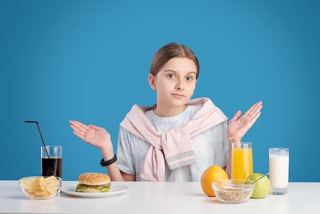 Retrato de uma adolescente confusa, encolhendo os ombros enquanto escolhe entre alimentos saudáveis e não saudáveis