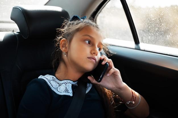 Retrato de uma adolescente falando em smartphone no carro, olhando pela janela. vestindo forma escolar.