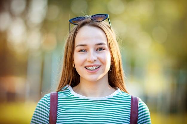 Retrato de uma adolescente feliz com close-up do aparelho no verão na rua. o conceito de cuidar da saúde, um sorriso lindo, corrigindo a má oclusão