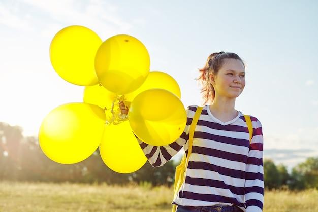 Retrato de uma adolescente feliz de 15 anos com balões amarelos. céu nas nuvens, fundo da natureza. férias, natureza, adolescentes, conceito de alegria