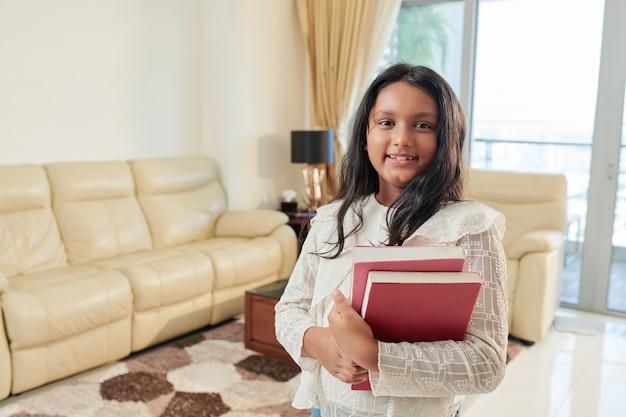 Retrato de uma adolescente indiana feliz com livros nas mãos, em pé na sala de estar e sorrindo para a câmera