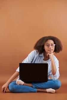 Retrato de uma adolescente mestiça sorridente com penteado afro, sentada com as pernas cruzadas, o laptop sobre os joelhos e a cabeça na mão inclinada