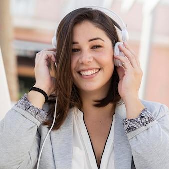 Retrato de uma adolescente posando com seus fones de ouvido