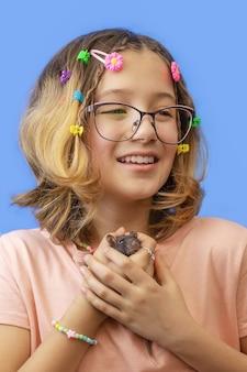 Retrato de uma adolescente segurando um rato de estimação em fundo azul, amor por roedores ou animais