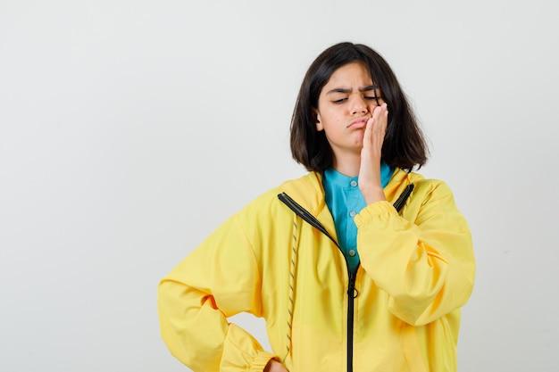 Retrato de uma adolescente sofrendo de uma terrível dor de dente, vestindo uma jaqueta amarela e olhando para baixo