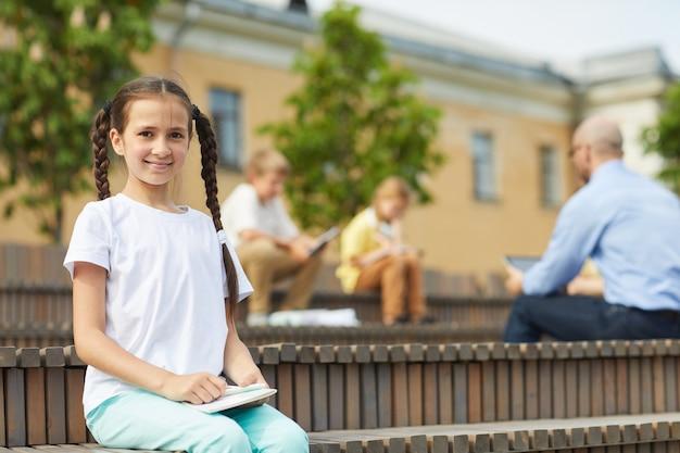 Retrato de uma adolescente sorridente, olhando para a câmera enquanto está sentado no banco ao ar livre com o professor dando aula no fundo, copie o espaço