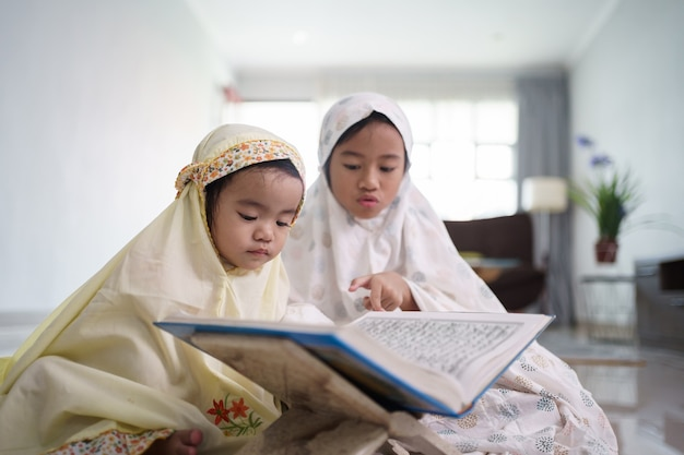 Retrato de uma adorável criança muçulmana lendo alcorão juntos em casa