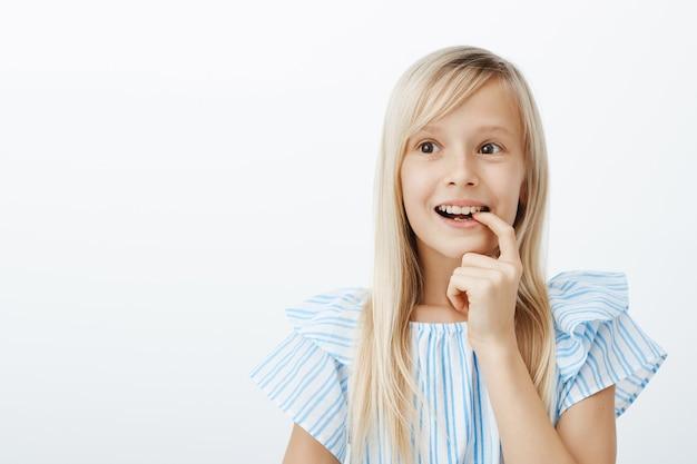 Retrato de uma adorável criança sonhadora com cabelos loiros, olhando para o lado e mordendo o dedo com um largo sorriso, imaginando