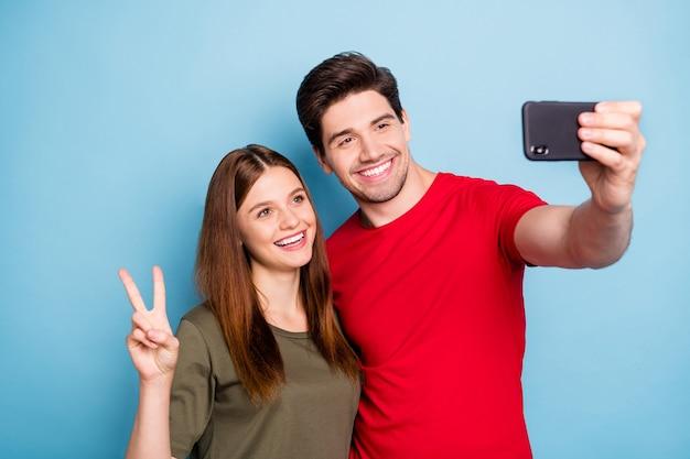 Retrato de uma adorável duas pessoas casadas blogueiras descansando relaxando no resort fazem selfie romance romântico usar camiseta verde vermelha isolada sobre fundo de cor azul