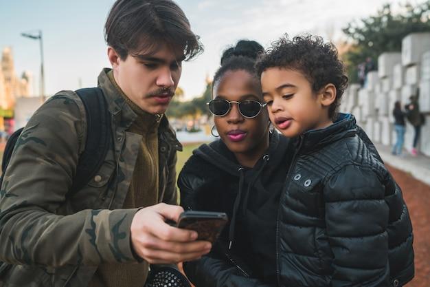 Retrato de uma adorável família étnica de raça mista, se divertindo, relaxando e usando o telefone celular ao ar livre do parque.