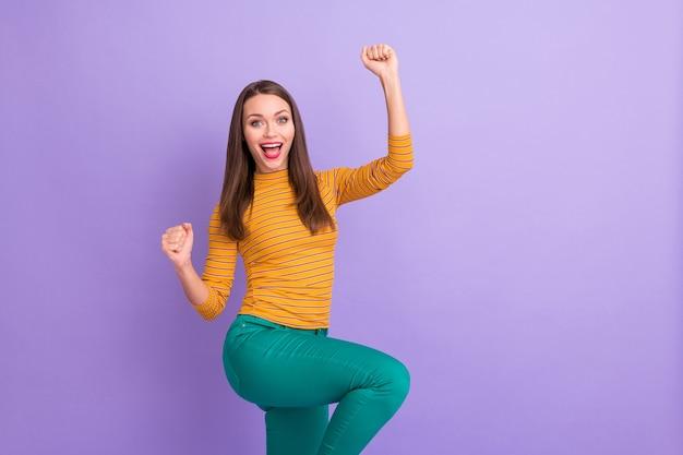 Retrato de uma adorável garota alegre em êxtase celebrando sua vitória na loteria levantar os punhos gritar sim, vestir um pulôver estilo casual isolado sobre a cor violeta violeta