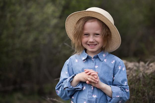 Retrato de uma adorável garota caucasiana de 5 anos de pé ao lado de uma árvore caída com raízes reviradas na floresta e parece reto