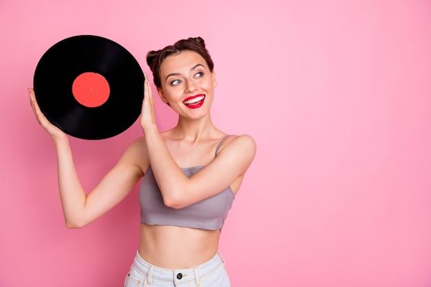 Retrato de uma adorável garota fofa amante da música segurando um disco de gramofone de placa de vinil deseja que uma festa retrô use roupas de estilo casual isoladas sobre a cor rosa