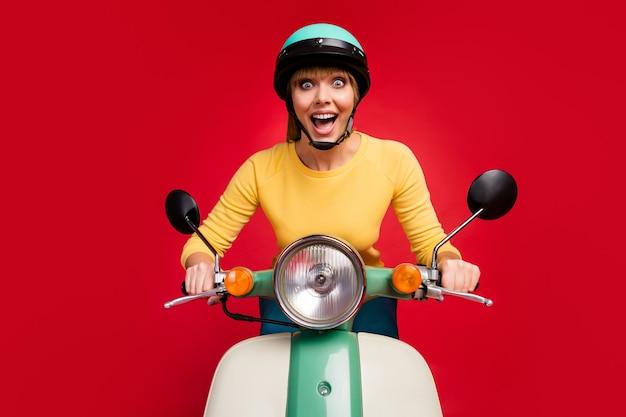 Retrato de uma adorável garota louca e feliz dirigindo uma motocicleta com rosto animado na parede vermelha