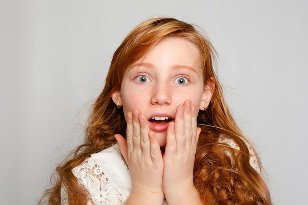 Retrato de uma adorável garota ruiva em um fundo cinza