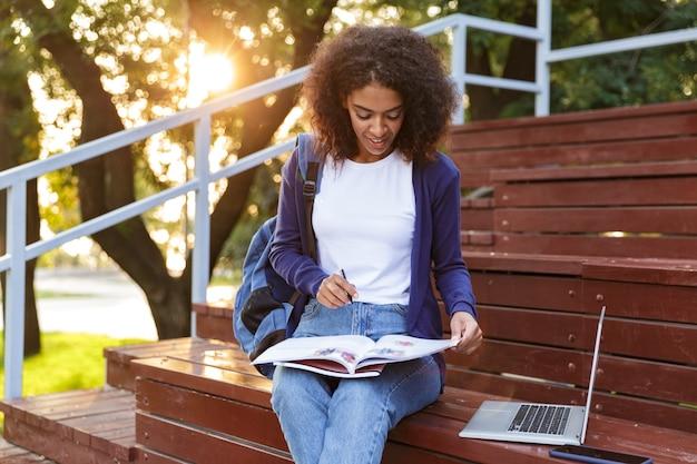 Retrato de uma adorável jovem africana com uma mochila descansando no parque, lendo uma revista