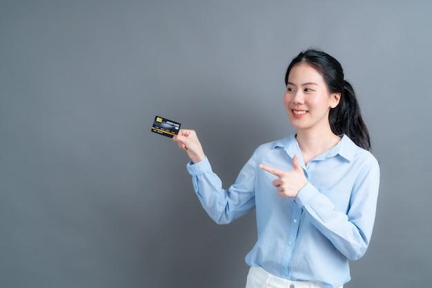 Retrato de uma adorável jovem asiática de camisa azul, mostrando o cartão de crédito com espaço de cópia na parede cinza
