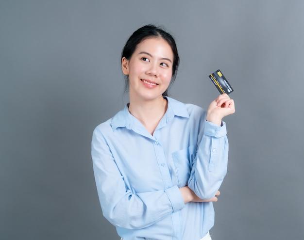 Retrato de uma adorável jovem asiática de camisa azul, mostrando um cartão de crédito com espaço de cópia